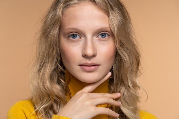 Jonge vrouw gezicht met blauwe ogen, krullend natuurlijk blond haar en wenkbrauwen, heeft geen make-up