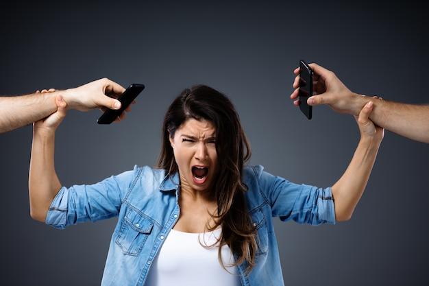 Jonge vrouw gillen en hand in hand met telefoons omdat ze geen telefoons in haar leven wil.