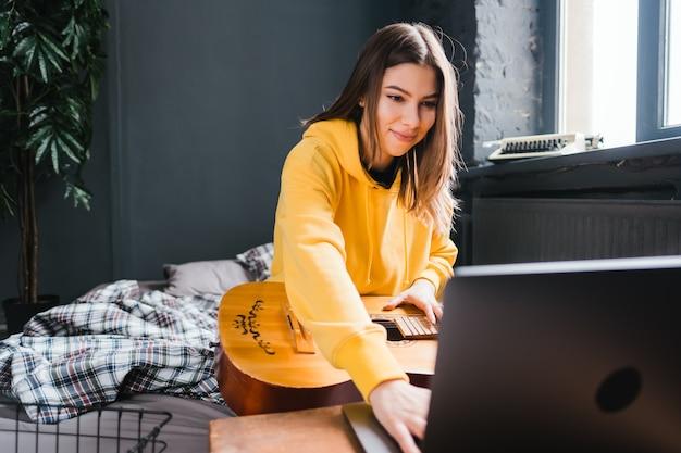 Jonge vrouw gitaar leren spelen thuis, kijken naar online cursussen met behulp van een laptop, zittend op het bed