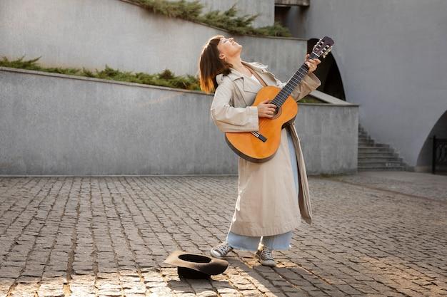 Jonge vrouw gitaarspelen buiten met kopie ruimte
