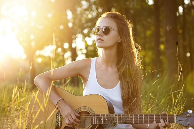 Jonge vrouw gitaarspelen in de natuur tijdens zonsondergang