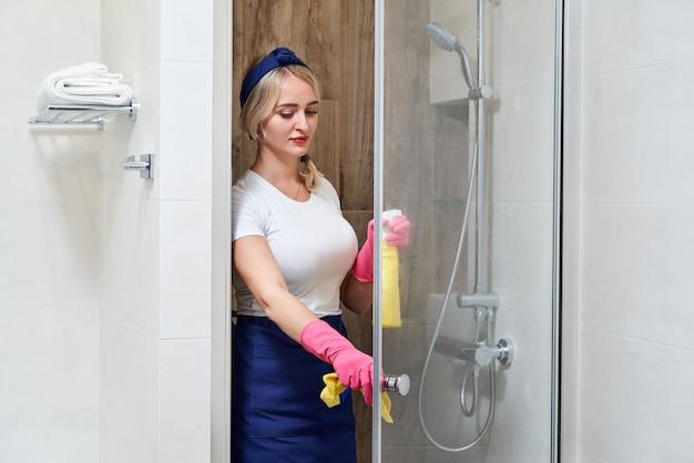 Jonge vrouw glazen douchecabine met spons en spray fles schoonmaken