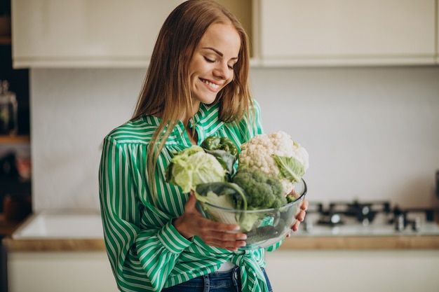 Jonge vrouw glimlachend en bloemkool te houden