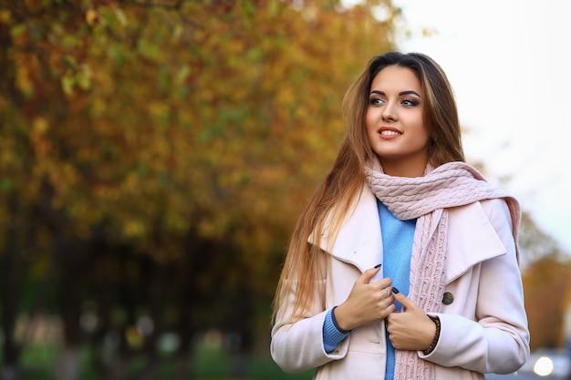 Jonge vrouw glimlachend en herfst gele esdoorn tuin achtergrond.