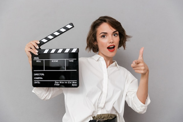 Jonge vrouw glimlachend en met zwarte filmklapper, geïsoleerd over grijze muur
