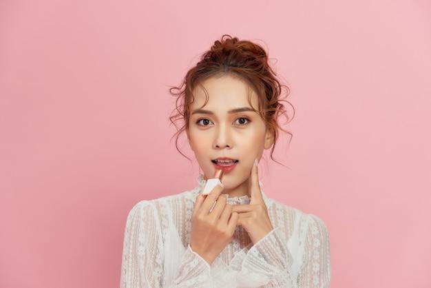 Jonge vrouw glimlachend en rode lippenstift op haar lippen toe te passen