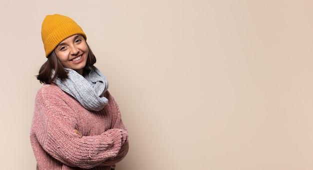 Jonge vrouw glimlachend naar camera met gekruiste armen en een gelukkige, zelfverzekerde, tevreden uitdrukking, zijaanzicht