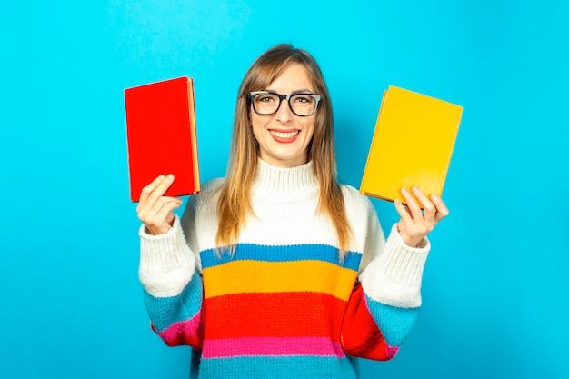 Jonge vrouw glimlacht en houdt boeken in haar handen op een blauwe achtergrond