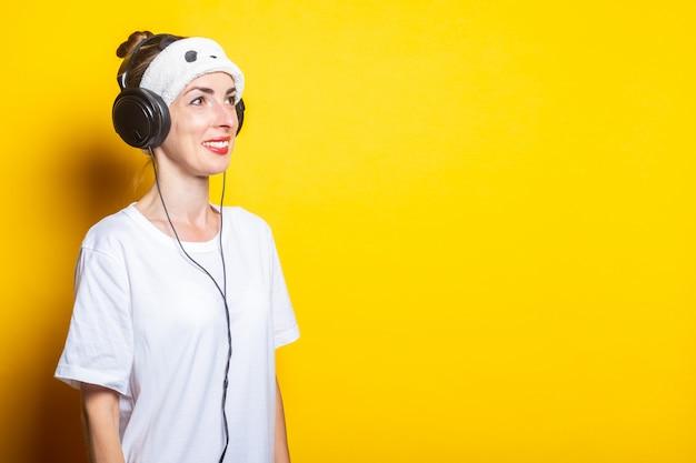 Jonge vrouw glimlacht in een slaapmasker en koptelefoon, luistert naar muziek.
