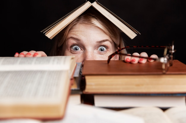 Jonge vrouw gluurt met grote ogen uit een stapel boeken met afschuw. onderwijs en training.