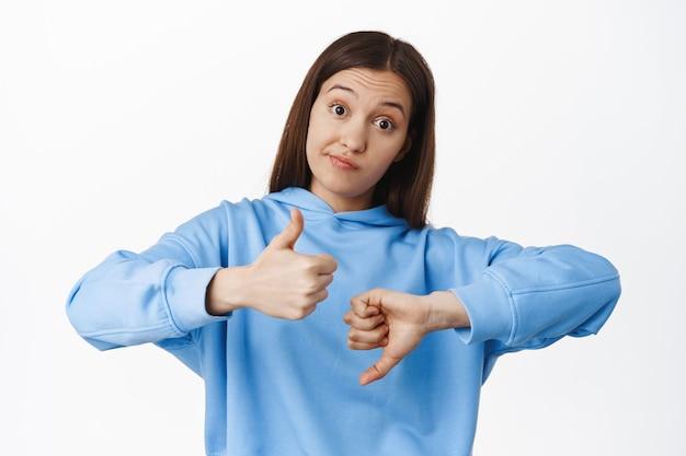 Jonge vrouw grijns, shows als afkeer, duimen omhoog en duim omlaag gebaar, gemiddelde beoordeling, gemiddeld resultaat, staande in hoodie tegen witte muur