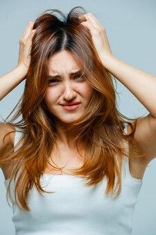 Jonge vrouw grijpt naar haar haar