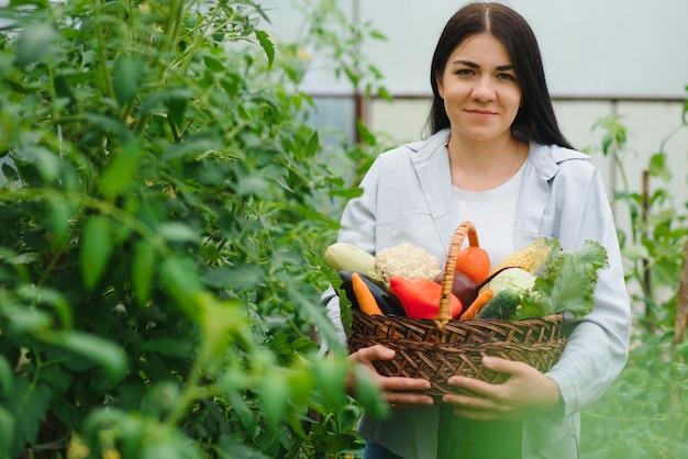 Jonge vrouw groenten plukken uit kas