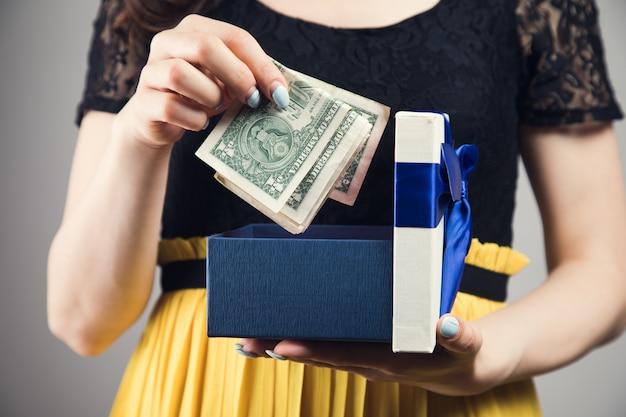 Jonge vrouw haalt geld uit een geschenkdoos