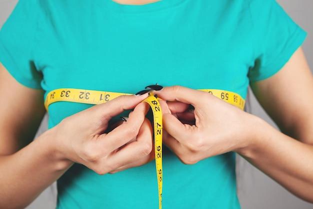 Jonge vrouw haar borsten meten met een tape