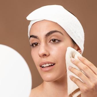 Jonge vrouw haar gezicht aan te raken met een handdoek