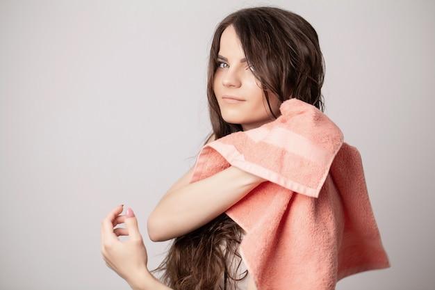 Jonge vrouw haar haren drogen met handdoek op lichte achtergrond.