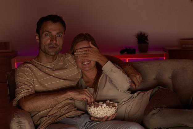 Jonge vrouw haar ogen sluiten met de hand tijdens het kijken naar enge film samen met haar vriendje en popcorn eten