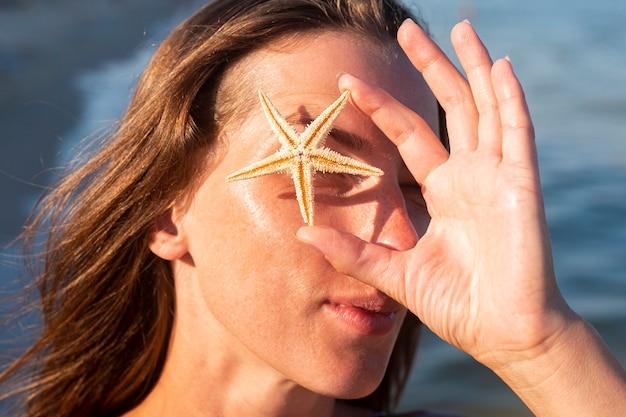 Jonge vrouw haar oog sluiten met zeester op de achtergrond van de zee.