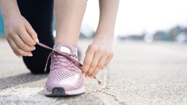 Jonge vrouw haar schoenveters binden op buiten training, weg