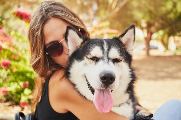 Jonge vrouw haar siberische husky knuffelen in park