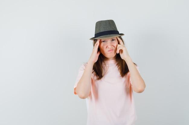 Jonge vrouw haar tempels in roze t-shirt, hoed wrijven en boos kijken. vooraanzicht.
