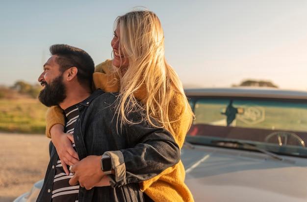 Jonge vrouw haar vriendje van achteren knuffelen tijdens het verblijf op de auto