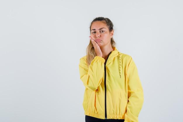 Jonge vrouw haar wang in gele regenjas aan te raken en pijnlijk te kijken