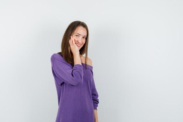 Jonge vrouw haar wang in violet overhemd aan te raken en verlegen te kijken. vooraanzicht.