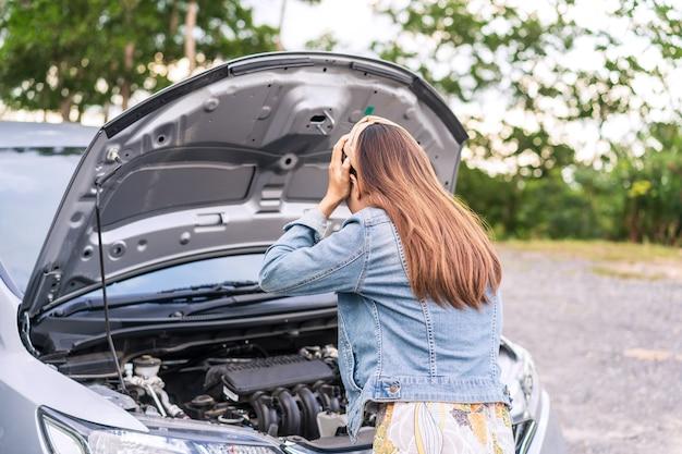 Jonge vrouw had een slechte autopech en voelde zich gefrustreerd tijdens het reizen