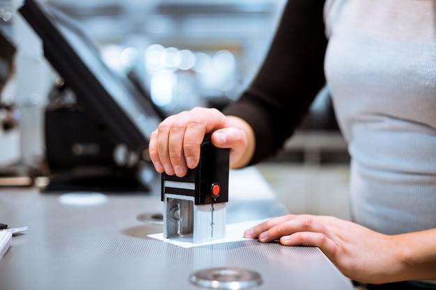 Jonge vrouw hand doen proces betaling, stempel met verkoop krijgen naar een ontvangstbewijs in het enorme winkelcentrum, financiën concept