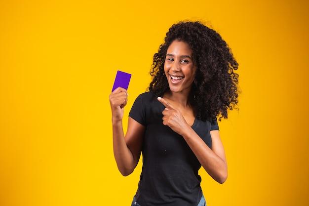 Jonge vrouw hand houdt paarse kaart mockup. vrouw met boodschappenkaart. mooie jonge vrouw met creditcard