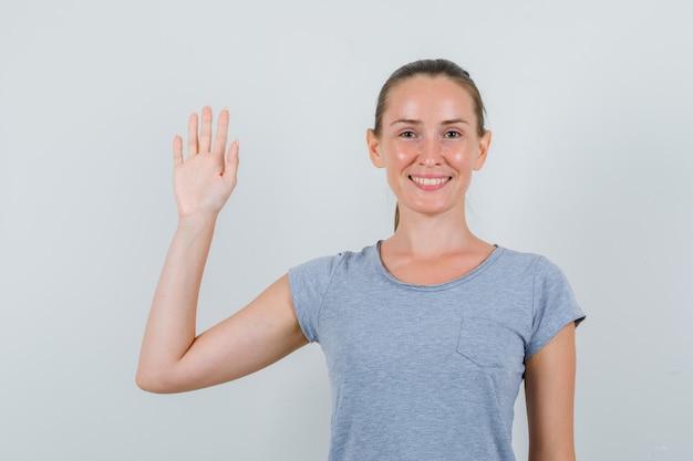 Jonge vrouw hand in grijs t-shirt zwaaien en op zoek vrolijk, vooraanzicht.
