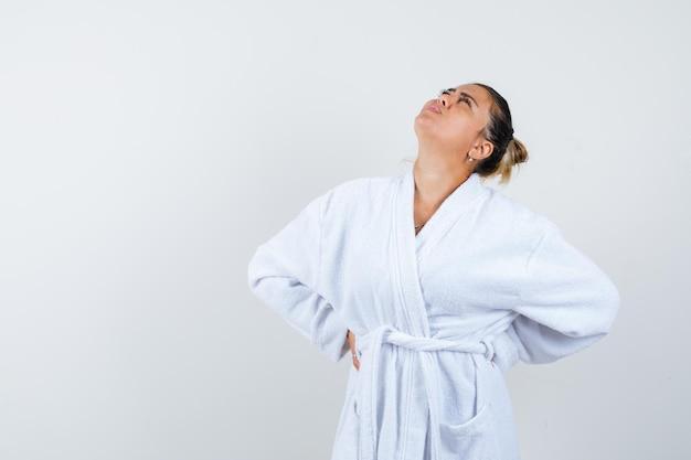 Jonge vrouw hand in hand achter haar middel, kijkt naar boven in witte badjas en ziet er mooi uit