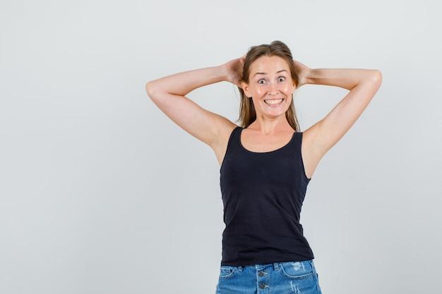 Jonge vrouw hand in hand achter het hoofd in hemd, korte broek en op zoek grappig