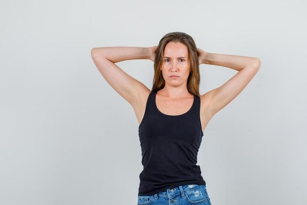 Jonge vrouw hand in hand achter het hoofd in hemd, korte broek en op zoek verdrietig