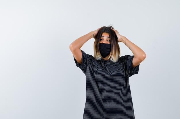 Jonge vrouw hand in hand achter het hoofd in zwarte jurk, zwart masker en op zoek naar gekwelde, vooraanzicht.