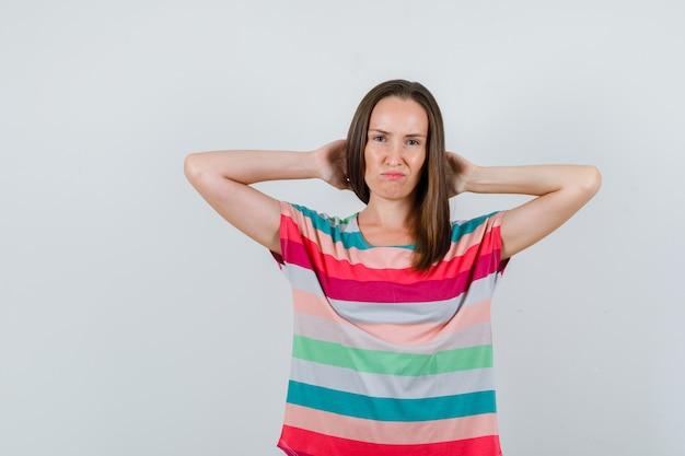 Jonge vrouw hand in hand achter hoofd in t-shirt en op zoek somber. vooraanzicht.