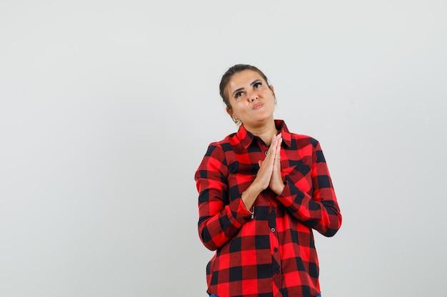 Jonge vrouw hand in hand biddend gebaar in ingecheckte overhemd en hoopvol op zoek. vooraanzicht.