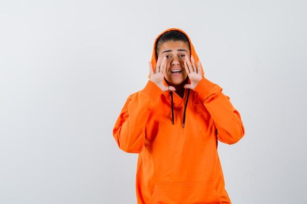 Jonge vrouw hand in hand bij de mond terwijl ze iemand in een oranje hoodie belt en er gefocust uitziet