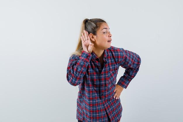 Jonge vrouw hand in hand dichtbij oor om iets in geruit overhemd te horen en gefocust te kijken