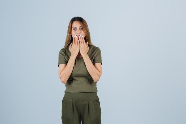 Jonge vrouw hand in hand in de buurt van mond in t-shirt, broek en verbaasd kijken. vooraanzicht.
