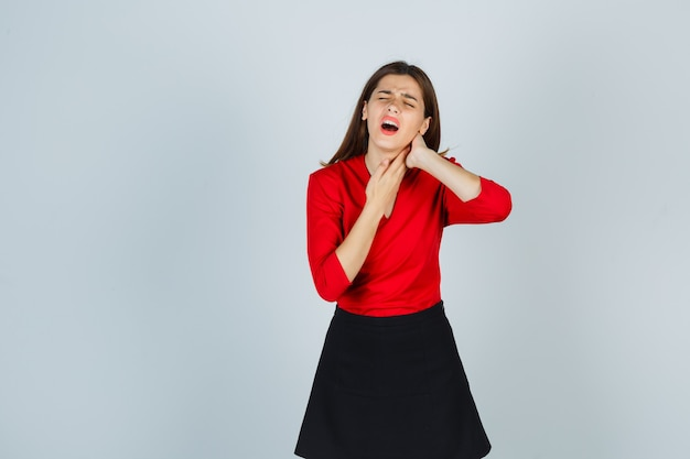 Jonge vrouw hand in hand in nek, met nekpijn in rode blouse