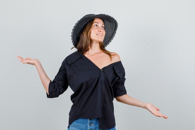 Jonge vrouw hand in hand om evenwicht in shirt, korte broek, hoed te vangen en er vrolijk uit te zien. vooraanzicht.