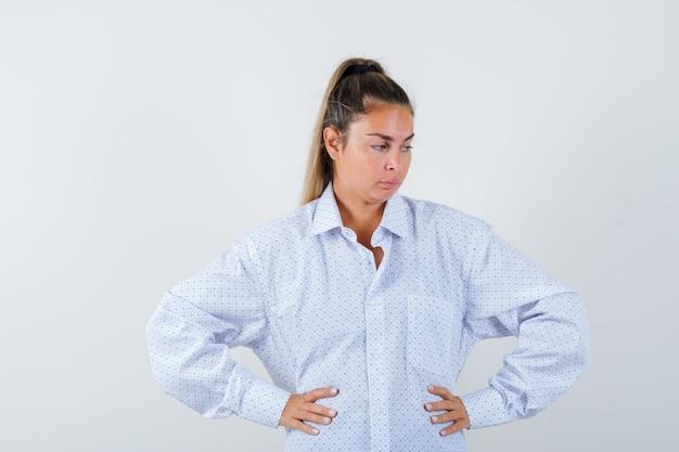 Jonge vrouw hand in hand op de heupen, denken aan iets in wit overhemd en peinzend kijken