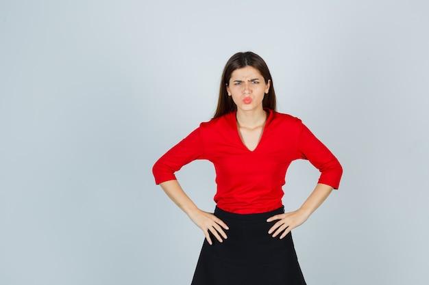 Jonge vrouw hand in hand op de heupen, grimassen in rode blouse, zwarte rok en boos kijken