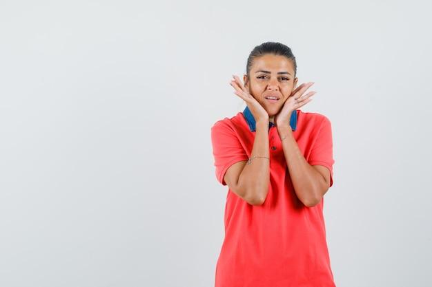 Jonge vrouw hand in hand op de wang in rood t-shirt en ziet er mooi uit, vooraanzicht.