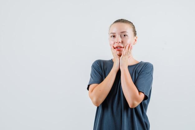 Jonge vrouw hand in hand op de wangen in grijs t-shirt en ziet er mooi uit