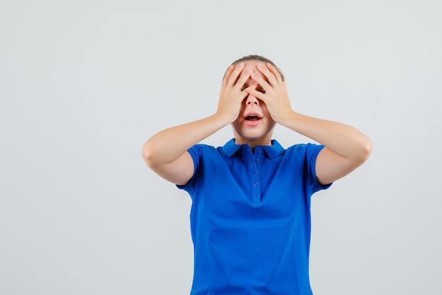 Jonge vrouw hand in hand op gezicht in blauw t-shirt en hoopvol kijkt