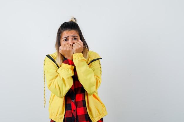 Jonge vrouw hand in hand op gezicht in geruit hemd, jas en ziet er bang uit, vooraanzicht.